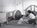 P 55, 1963 Ms P Chapman, Asst Chief Physio w a retarded child in Physio Building